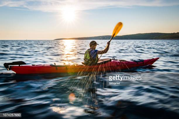 kayaker rowing in sea - kayak stock pictures, royalty-free photos & images