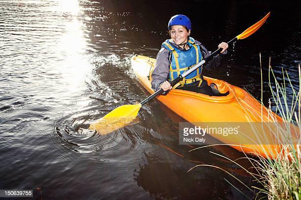 Kayaker rowing in still lake