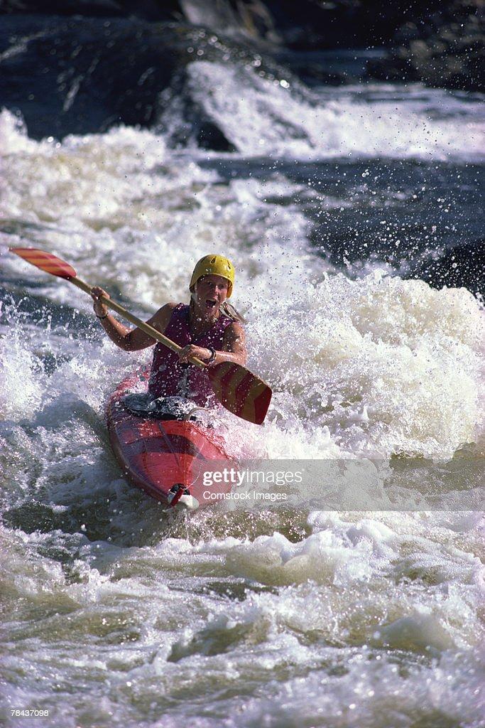 Kayaker rowing in whitewater : Stockfoto