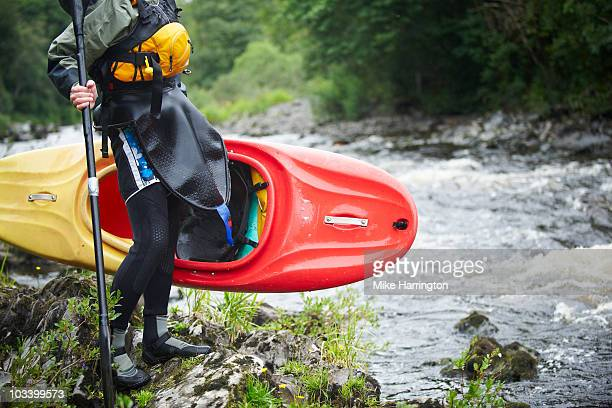 kayaker standing on river edge - newpremiumuk stock pictures, royalty-free photos & images
