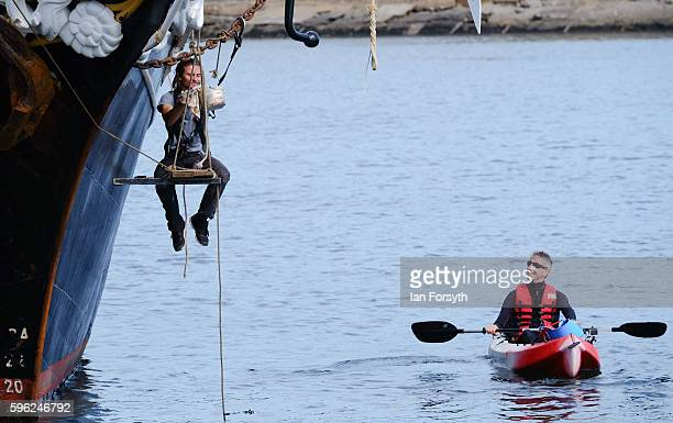 A kayaker stops to watch a crew member as he paints the side of the ship during the North Sea Tall Ships Regatta on August 27 2016 in Blyth England...