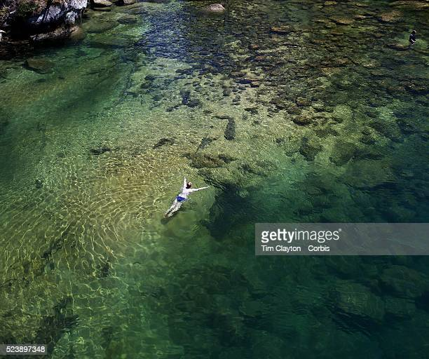 A kayaker takes a break and enjoys a swim in the crystal clear waters of a sheltered lagoon in the Abel Tasman National Park South Island New Zealand...