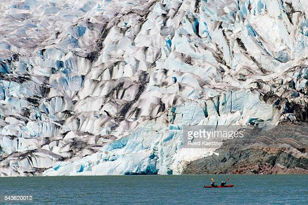 Kayakers are dwarfed by the Mendenhall Glacier just north of Juneau, Alaska