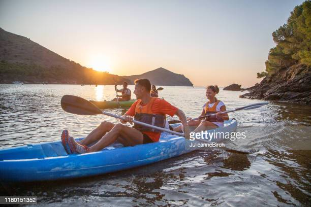 kayakers nearing shore as sun sets over mediterranean - sea kayaking stock pictures, royalty-free photos & images
