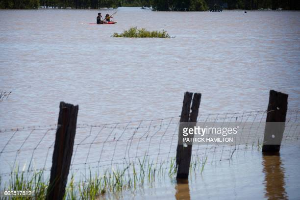 Kayakers paddle on the flooded Logan River caused by Cyclone Debbie as it flows over the Mt Lindesay Highway in Waterford West near Brisbane on April...