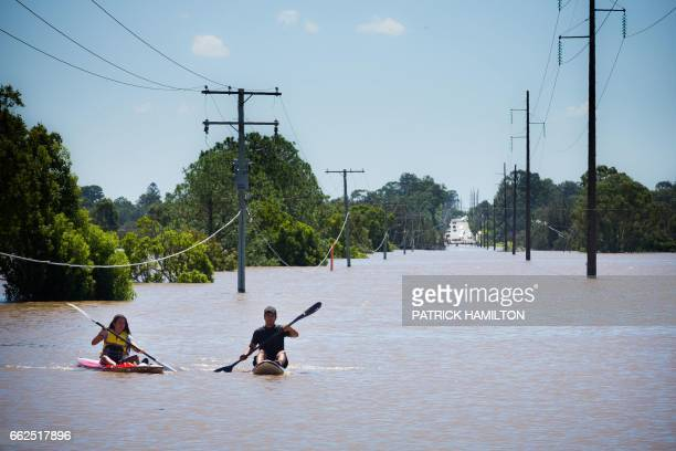TOPSHOT Kayakers paddle on the flooded Logan River caused by Cyclone Debbie as it flows over the Mt Lindesay Highway in Waterford West near Brisbane...