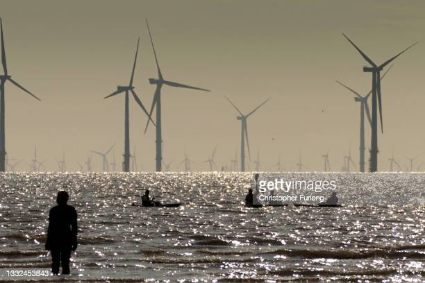 Kayakers paddle on the Mersey Estuary near the Burbo Bank Offshore Wind Farm on August 04, 2021 in Liverpool, United Kingdom.