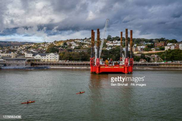 Kayakers paddle towards a huge construction machine at Dawlish train station where work has begun building a new and bigger sea wall to protect the...