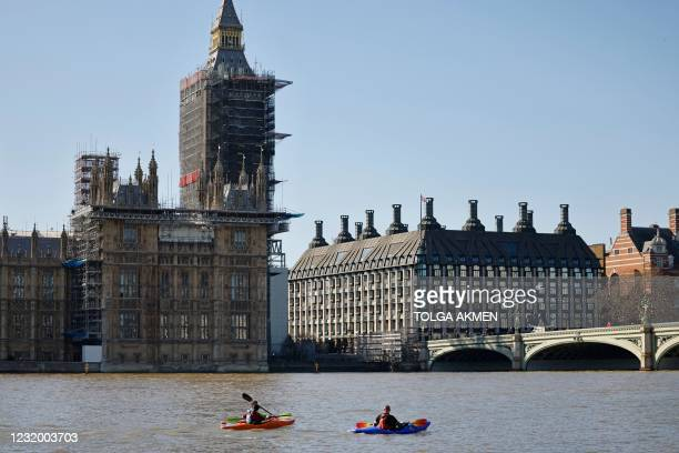 Kayakers pass the Palace of Westminster, home to the Houses of Parliament on the River Thames in London on March 29 as England's third Covid-19...