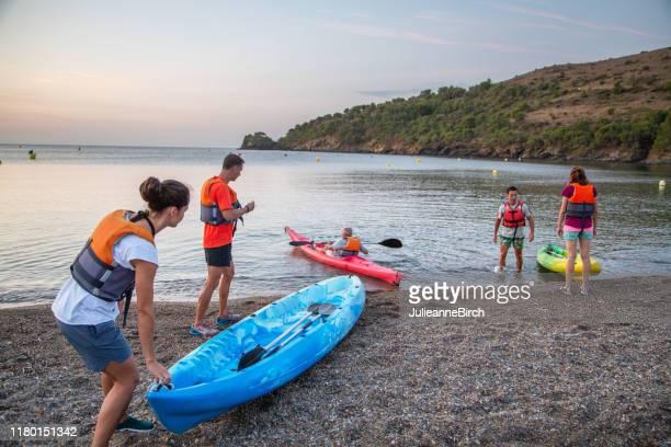 kayakers preparing to paddle in mediterranean at sunset - sea kayaking stock pictures, royalty-free photos & images