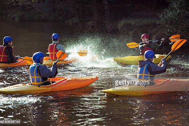 kayakers rowing together on still lake - water sport stock photos and pictures
