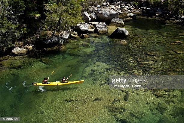 Kayakers venture down crystal clear waters of a sheltered lagoon in the Abel Tasman National Park South Island New Zealand The Abel Tasman National...