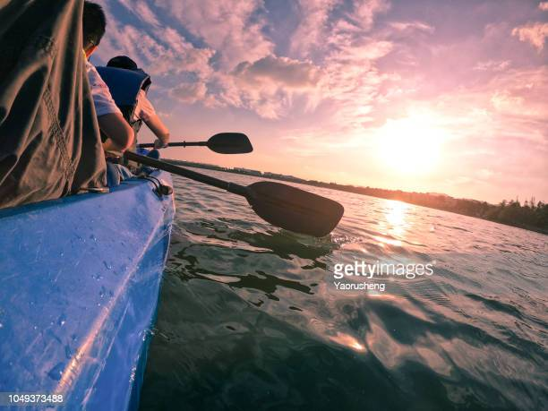 kayaking concept with family of mother and son swimming at sea at sunset time - ningbo stock pictures, royalty-free photos & images