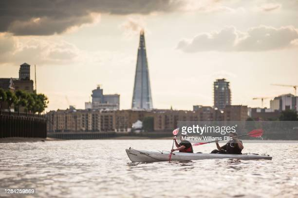 Kayaking on the River Thames in front of the Shard at sunset, London, England.