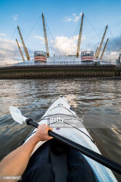 Kayaking on the River Thames past the O2 Arena, Greenwich, London, England.