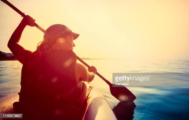 kayaking on the sea at sunset - sea kayaking stock pictures, royalty-free photos & images