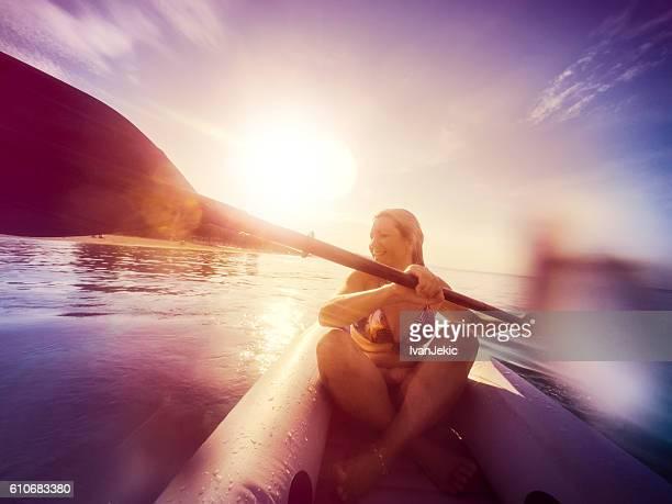 Kayaking on the sea at sunset with water splashing