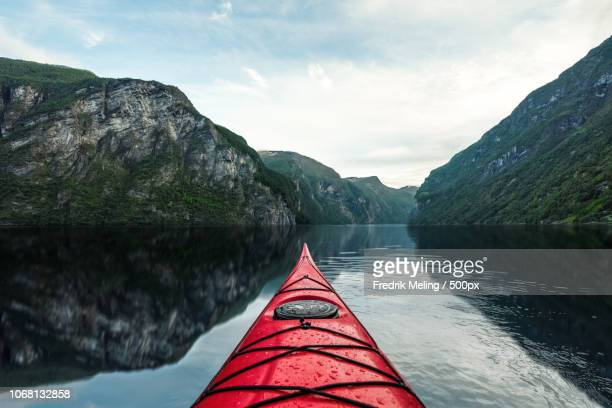 kayaking on water reflecting mountains - kajak stock-fotos und bilder