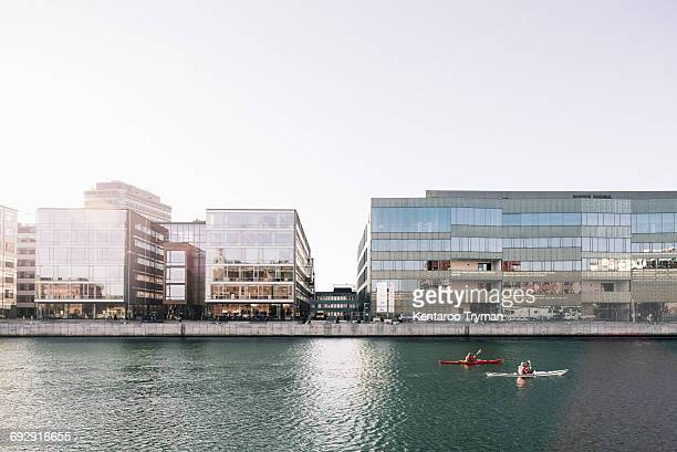 Kayaking over river in city against clear sky
