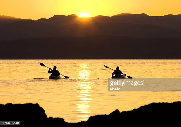 Kayaking sporty outdoor couple sea-canoeing at sunset