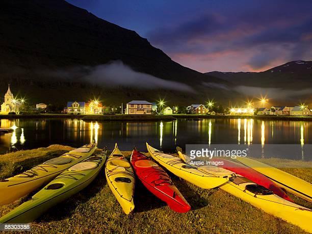 Kayaks by lake in Seydisfjordur, Iceland at night