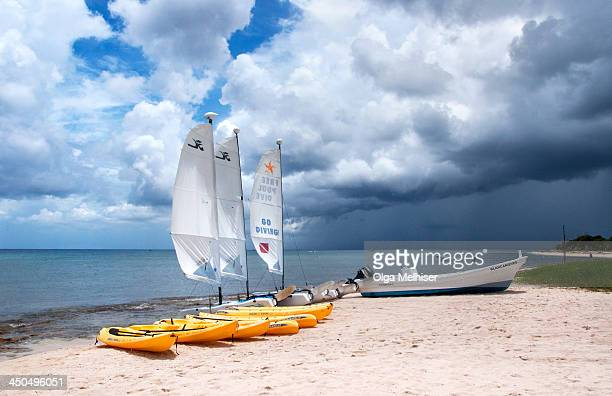 CONTENT] Kayaks hobie cats and motor boats are laying on the beach while a tropical shower is passing by in the background