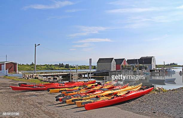 Kayaks moored on shore with old fisherman's dwellings in background - Blue Rocks, Nova Scotia