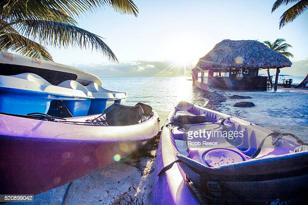kayaks on a resort beach in belize at sunrise - robb reece stock pictures, royalty-free photos & images
