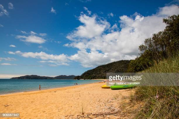 kayaks on golden sandy beach with blue sky in background, Abel Tasman National Park