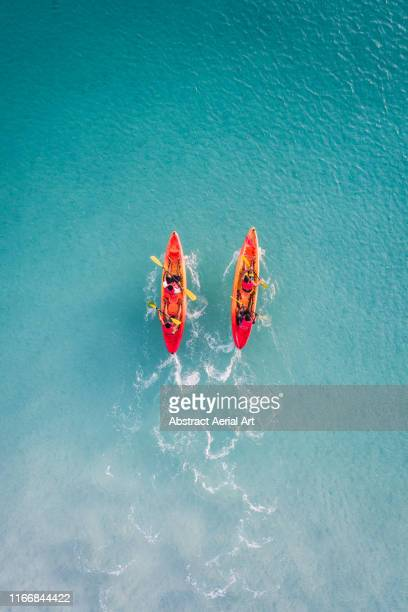 kayaks racing in shallow ocean water as seen from above, barbados - barbados stock pictures, royalty-free photos & images