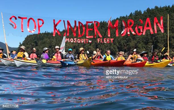 'Kayaktivists' hold up banner protesting plans by Kinder Morgan to build a pipeline during a waterbased pipeline resistance training camp held by...