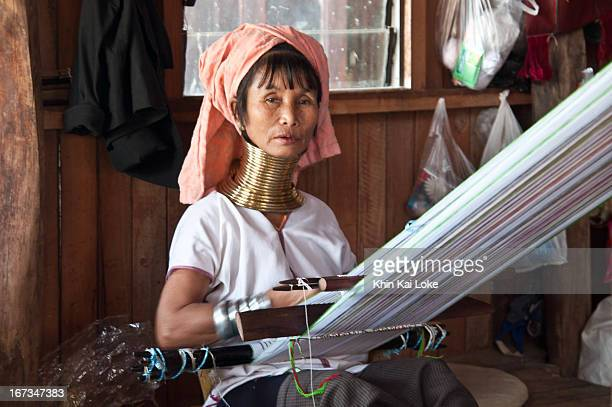 Kayan Lahwi with her distinctive golden rings around her elongated neck works at a cloth shop