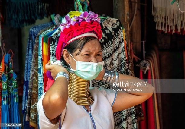 A Kayan woman fixes her protective facemask as she waits for tourists at her shop in Chang Siam Park in Pattaya on February 12 2020 Chang Siam Park...