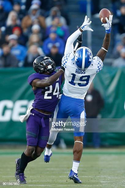 Kayaune Ross of the Kentucky Wildcats attempts to make a catch over Montre Hartage of the Northwestern Wildcats during the Music City Bowl at Nissan...