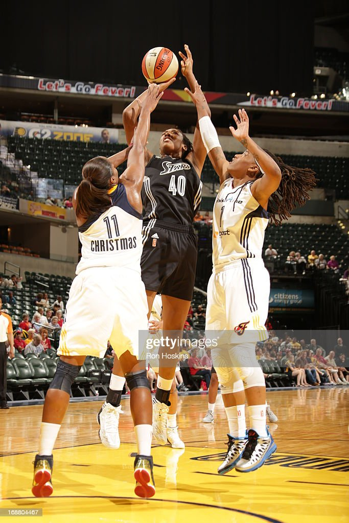 Kayla Alexander #40 of the San Antonio Silver Stars shoots over Karima Christmas #11 and Shavonte Zellus #1 of the Indiana Fever on May 13, 2013 at Bankers Life Fieldhouse in Indianapolis, Indiana.
