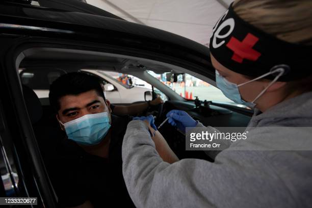 Kayla Cox, LVN, right, gives Silvestre Dionocio, left, a vaccine at the LA County Covid-19 vaccine site located at the County Office of Education on...