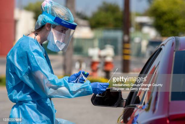 Kayla Ferrari a Physician Assistant with AltaMed Health Services prepares to test a drivethrough patient for COVID19 at their Bristol Street clinic...