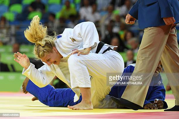 US Kayla Harrison celebrates after defeating France's Audrey Tcheumeo during their women's 78kg judo contest gold medal match of the Rio 2016 Olympic...