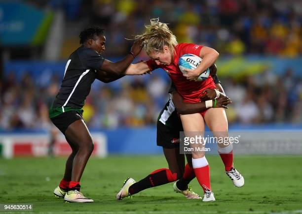 Kayla Moleschi of Canada is tackled by Janet Okelo of Kenya and Celestine Masinde of Kenya during the Rugby Sevens Women's Pool A match between...