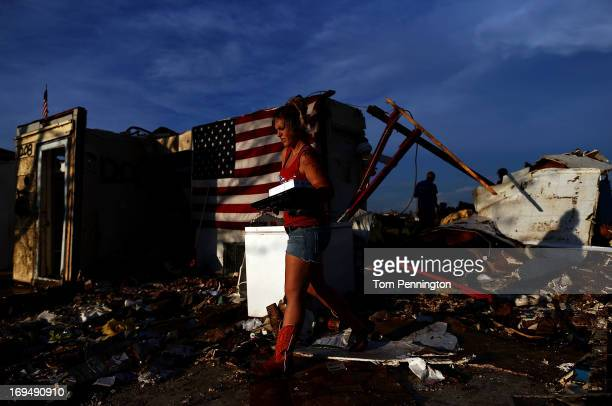 Kayla Murchie helps a friend salvage valuables from a tornado ravaged home on May 25 2013 in Moore Oklahoma The tornado of EF5 strength and two miles...