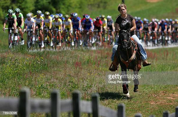 Kayla Newberry and her horse Troy keep pace with the peloton as they pass by her home in Social Circle during Stage Six of the Tour de Georgia on...