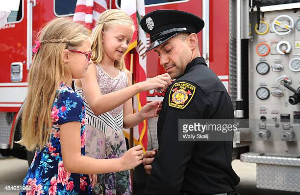 Kayla Rankell left and her sister Cheyanne pin a badge on their father LA City Fire graduate Nik Rankell during graduation ceremonies on August 20...