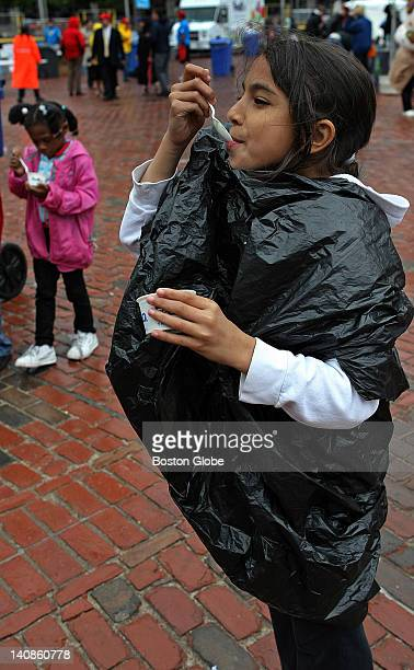 Kayla Strishock a student at Fletcher Maynard Academy in Cambridge wrapped in a trash bag to keep warm and dry so she can eat her ice cream The 27th...