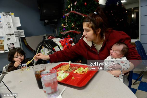 Kayle Quillen right holds her tiny 2 month old son Jesus right while she feeds her son Omar during dinner at the Samaritan House on December 17 2018...