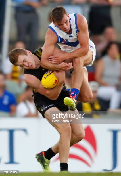 Kayne Turner of the Kangaroos and Jacob Townsend of the Tigers collide as they compete for the ball in the 2nd quarter during the AFL JLT Community...