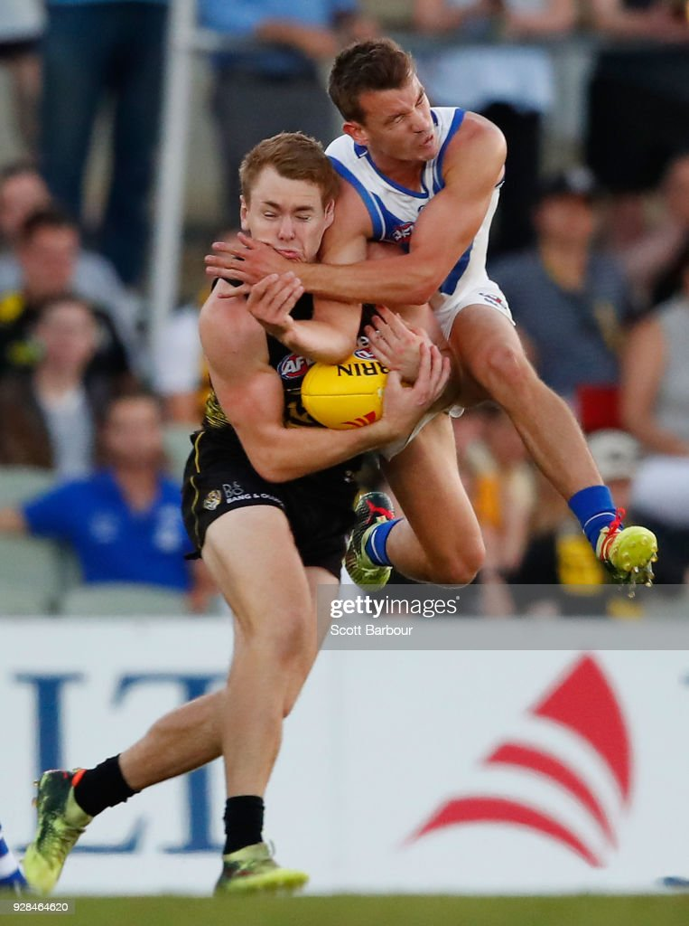 Kayne Turner of the Kangaroos and Jacob Townsend of the Tigers collide as they compete for the ball in the 2nd quarter during the AFL JLT Community Series match between the Richmond Tigers and the North Melbourne Kangaroos at Ikon Park on March 7, 2018 in Melbourne, Australia.