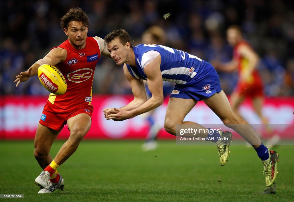 Kayne Turner of the Kangaroos handpasses the ball ahead of Jarrod Harbrow of the Suns during the 2018 AFL round 16 match between the North Melbourne Kangaroos and the Gold Coast Suns at Etihad Stadium on July 08, 2018 in Melbourne, Australia.