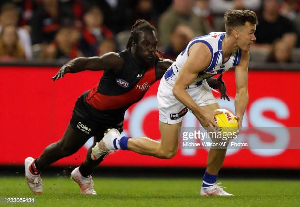 Kayne Turner of the Kangaroos is tackled by Anthony McDonald-Tipungwuti of the Bombers during the 2021 AFL Round 10 match between the Essendon...
