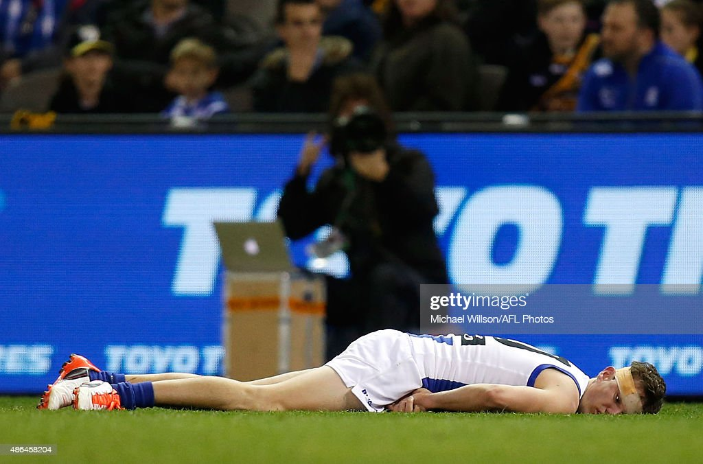 Kayne Turner of the Kangaroos lays injured during the 2015 AFL round 23 match between the Richmond Tigers and the North Melbourne Kangaroos at Etihad Stadium, Melbourne, Australia on September 4, 2015.