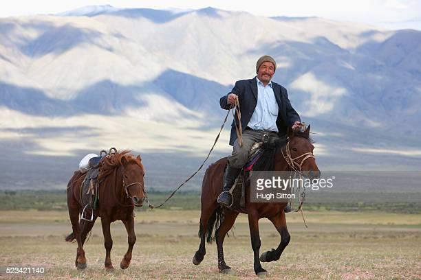 kazak man with horses - hugh sitton stock-fotos und bilder